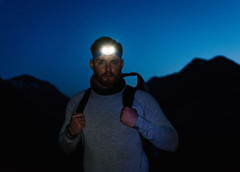 Man wearing head torch in the mountains at blue hour.