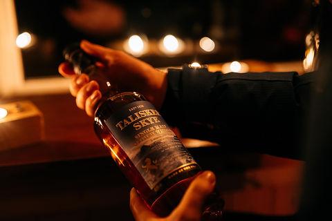 Man holding a bottle of Talisker whisky bottle.