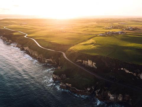 The sun rising over the Causeway Coast in Ireland.