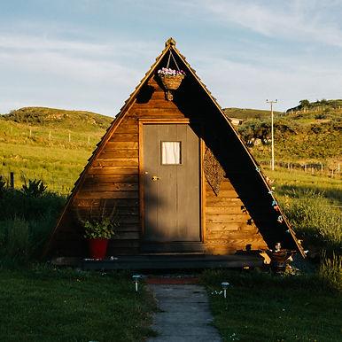 An A frame log cabin during golden hour