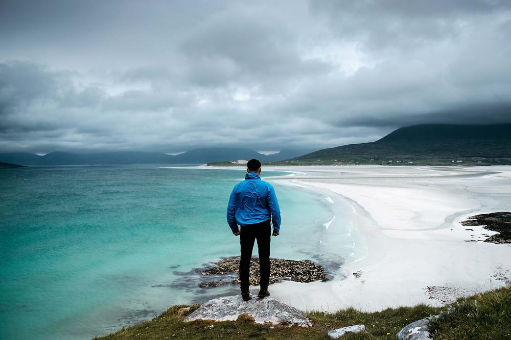 Man in blue jacket overlooking a white sandy beach on Harris, Scotland.