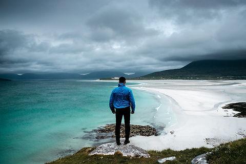 Man overlooking a windswept beach on the Isle of Harris.