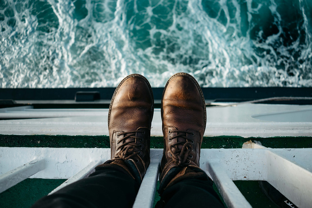 A birdseye view of brown leather boats, overlooking turquoise water on a boat trip.