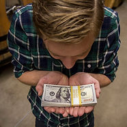 Child holding stack of cash