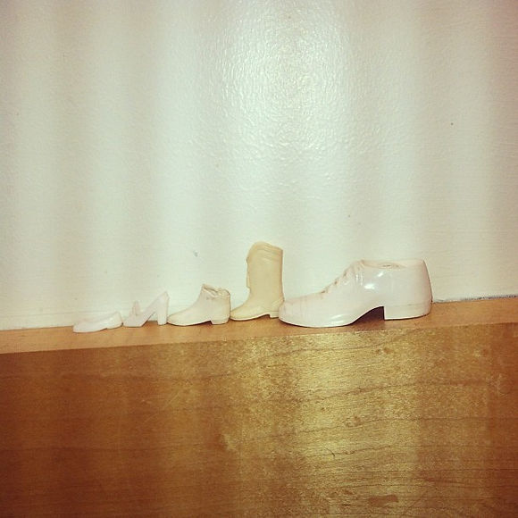 A strange line of lost (_) white shoes by my workstation at the library.jpg