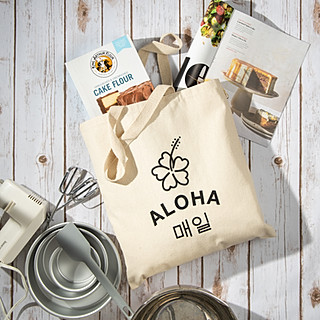 Aloha.Maeil tote bag on light-colored wood with baking tools