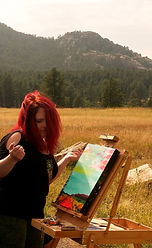 A female artist with bright red hair paints a landscape in a beautiful mountain vista.