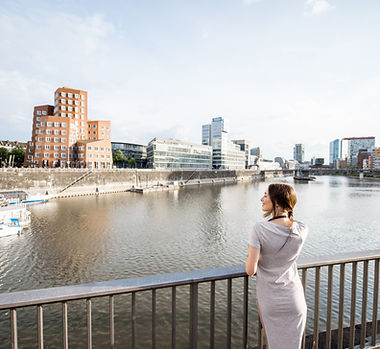 Young woman enjoying great view on the harbor with modern buildings in Dusseldorf city, Ge