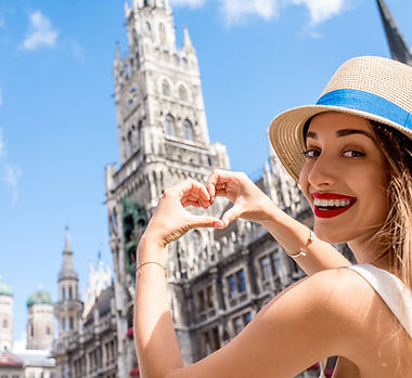 Young female tourist making heart shape with hands on the town hall building background in