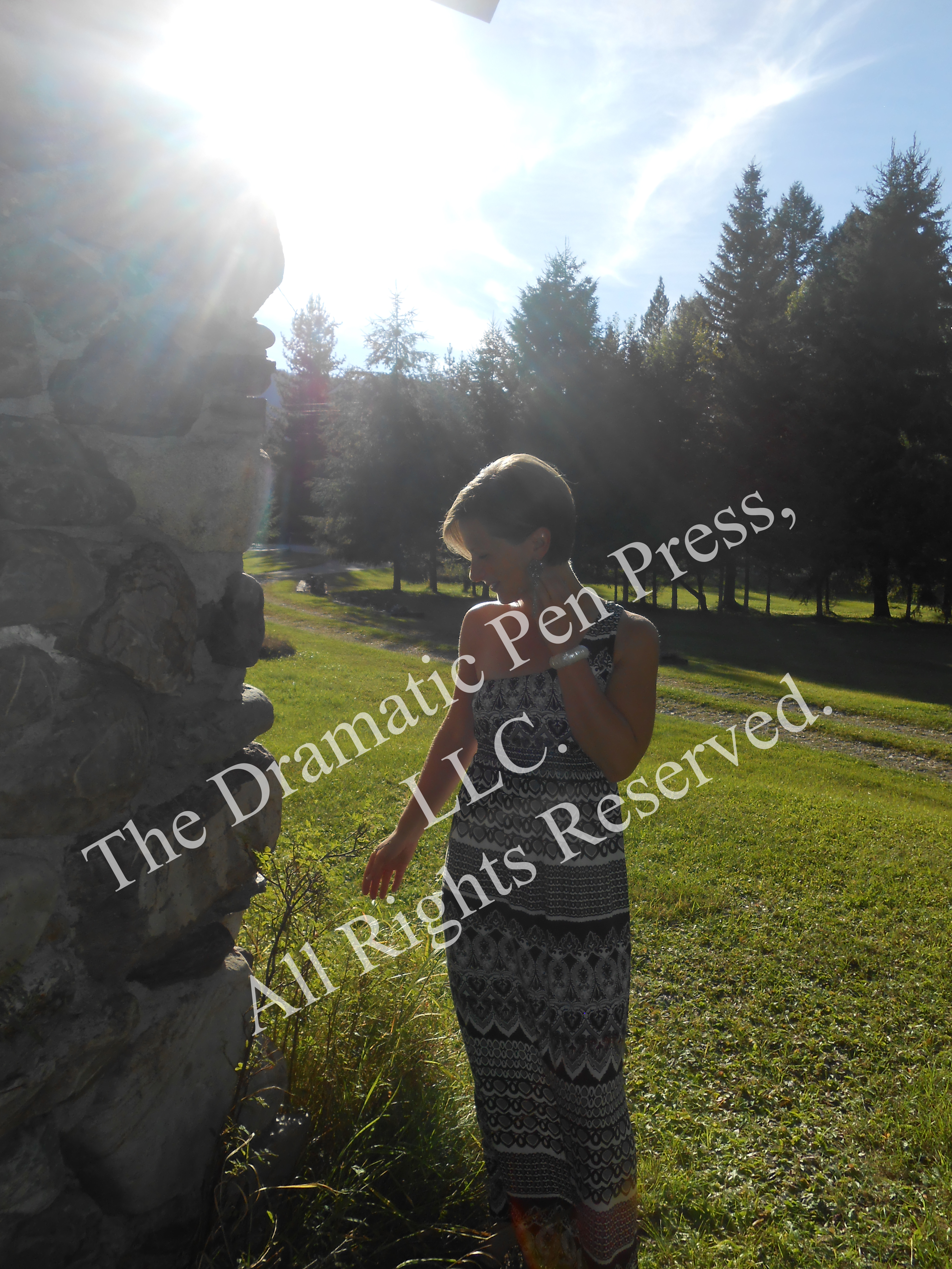 Woman in Sun by Stone Wall