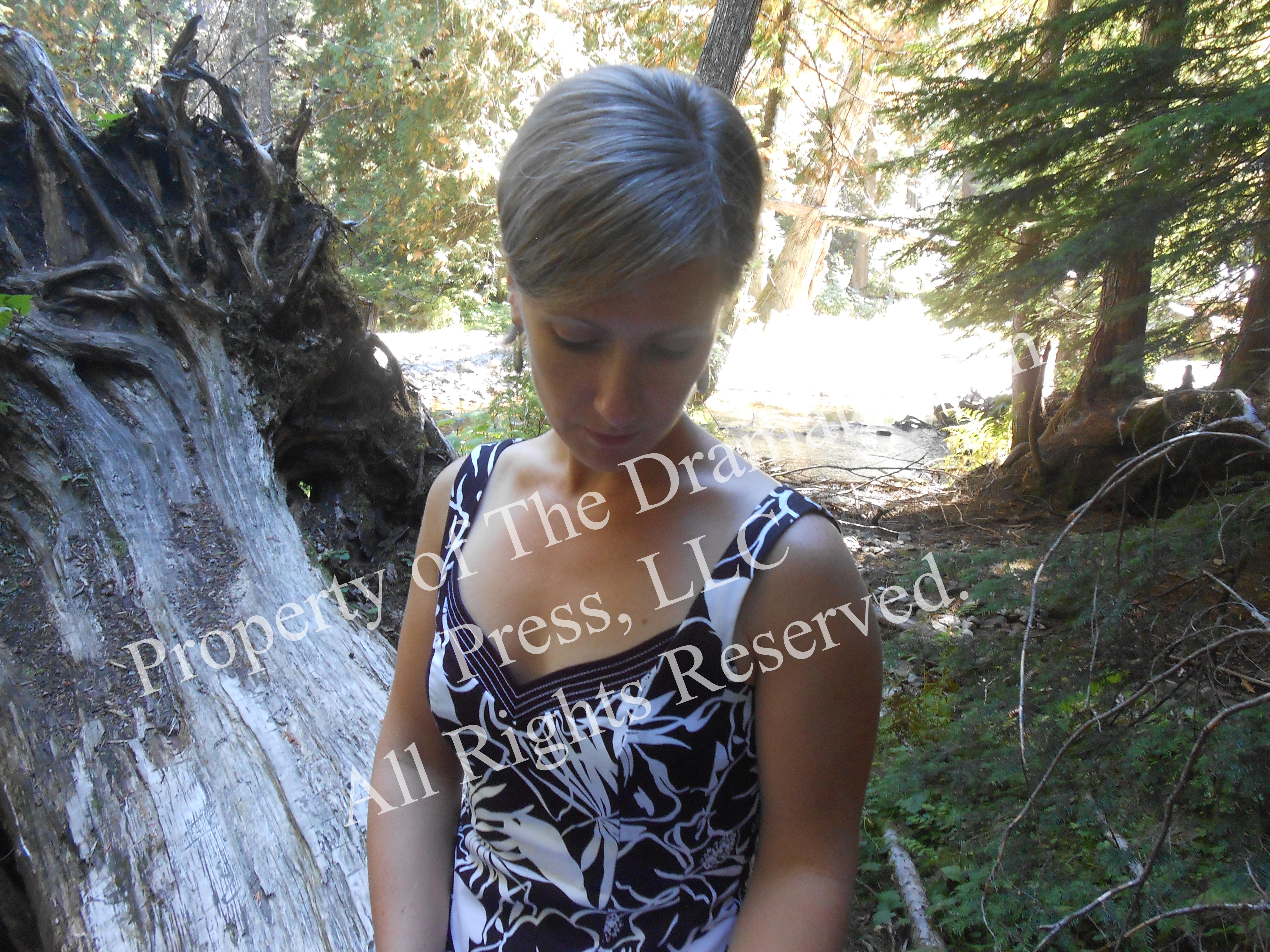 Woman Sitting in Woods Looking Down