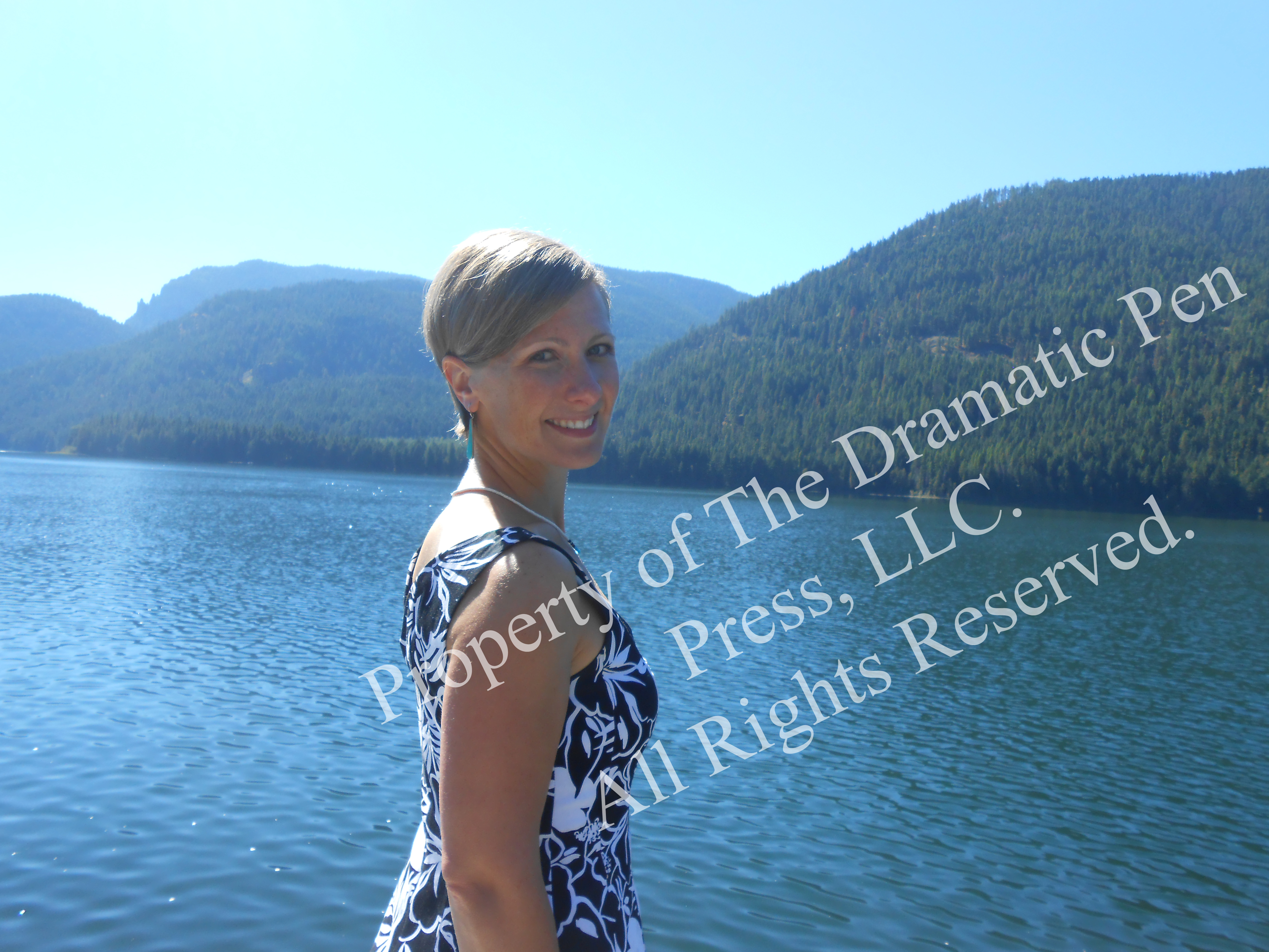 Smiling Woman by Water & Mountains
