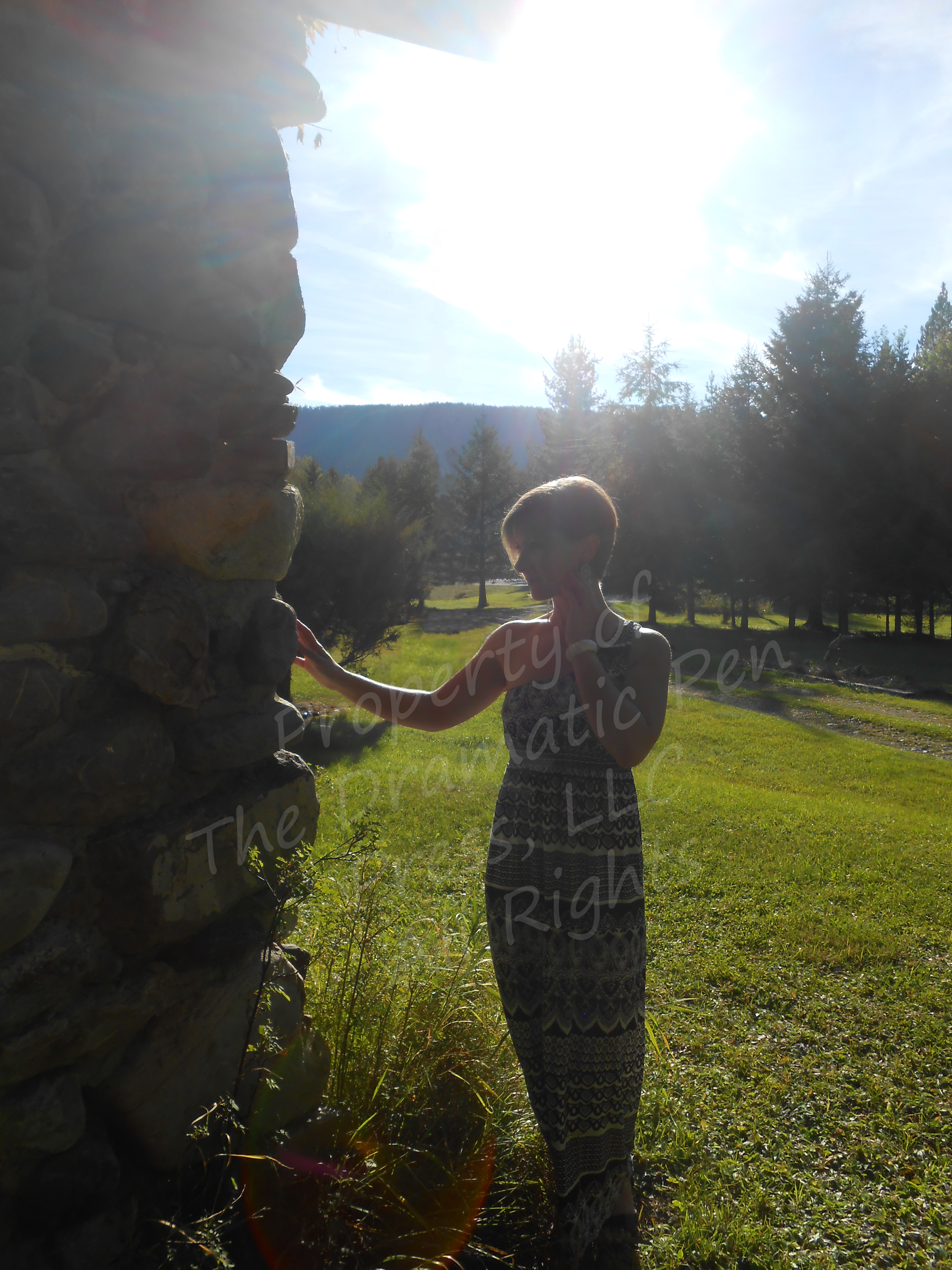 Woman Standing in Sun by Stone Wall