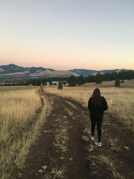 Person walks down weedy path towards mountainous backdrop.