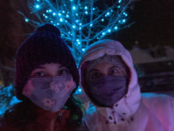 Olivia Ragan and her Mom in full winter gear and face masks in front of a lighted tree at the Denver Botanic Gardens.