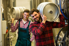 Portrait of brewers carrying keg on shou