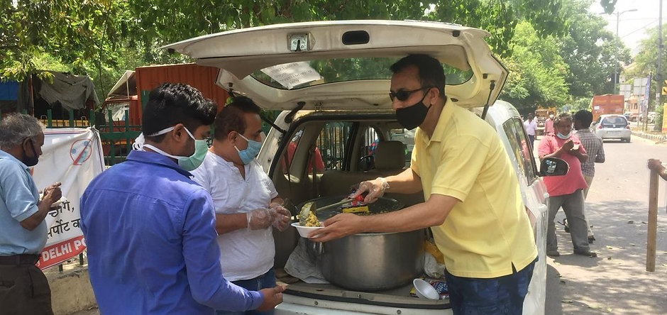 Residents Distributing Home Cooked Food to the Poor of the colony