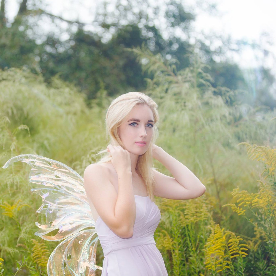 blonde in chiffon dress with fairy wings in a field of golden flowers