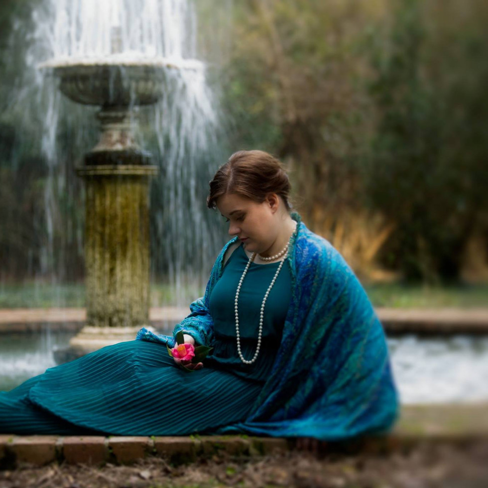 Lady in blue sitting in front of fountain.