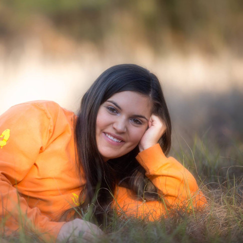 Young woman laying in grassy field.