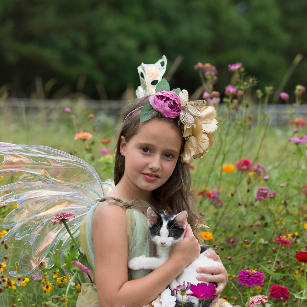 Little fairy playing with kitty in the flowers