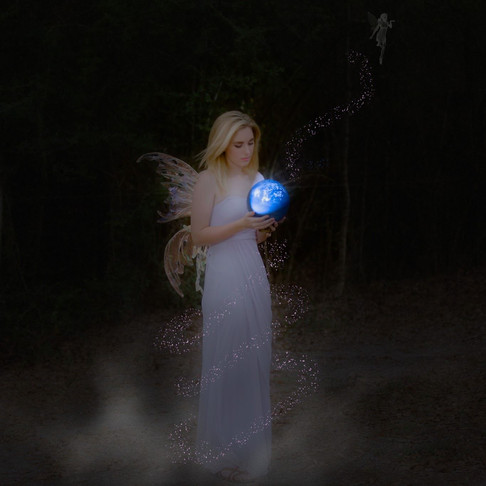 Young woman in the dark, with a glowing blue ball