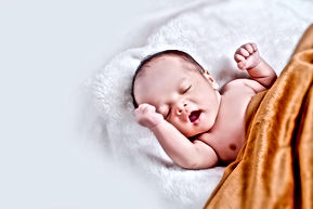 baby-lying-on-white-fur-with-brown-blank