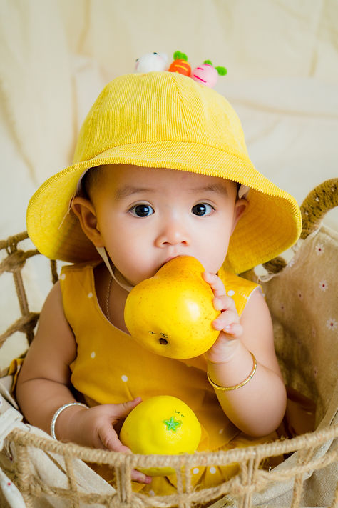 toddler-in-yellow-top-and-hat-holding-fruit-2869318.jpg