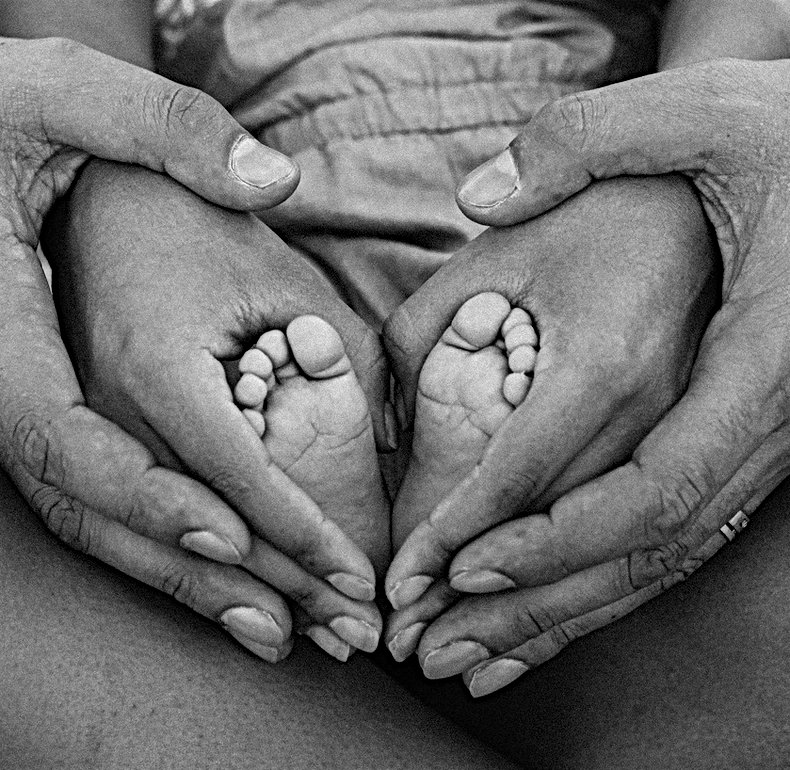 grayscale-photo-of-person-holding-feet-a
