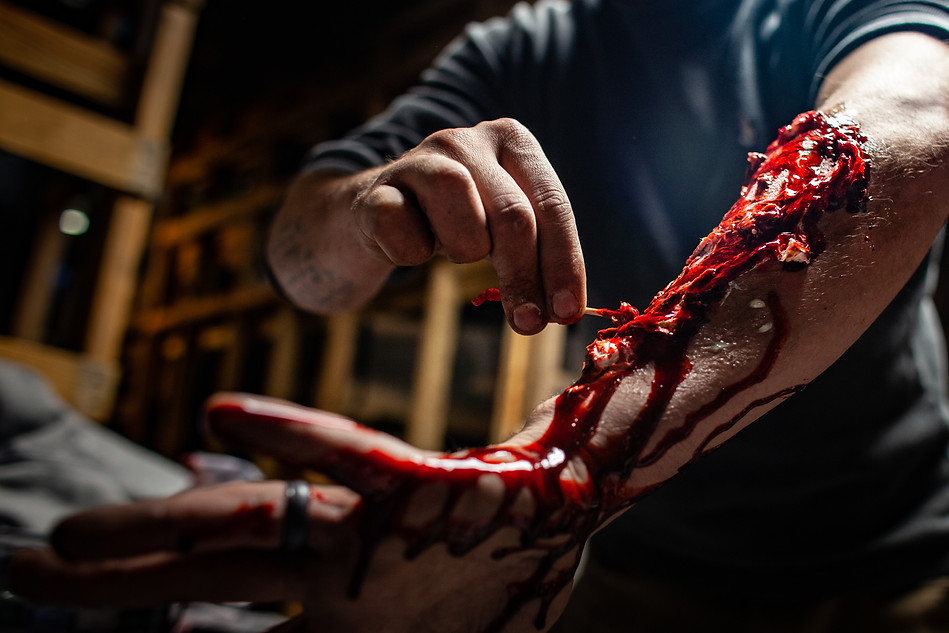 Lykins creates a fake wound on his arm- using liquid latex for a three dimensional effect. Adding plenty of blood red and other colors get the effect of gore. Lykins instructed actors in how to make their own wounds to facilitate more efficient pre-opening evenings.