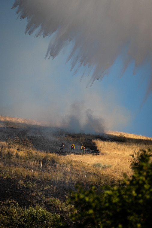 Three firefighters battle a bush fire on Mount Sentinel outside of Missoula, Montana as a helicopter drops water from the Clark Fork River on the area. The blaze started near the University of Montana housing villages on Aug. 20, 2020 and spread up the hill, stopping at the fire road. It was started by two children playing with a lighter behind the housing buildings.