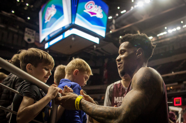 Rorie signs autographs for gathered basketball fans after the practice, before he heads to the locker room.