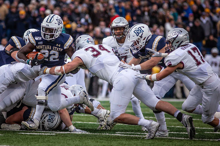 Montana State University running back Isaiah Ifanse attempts to get the ball through the University of Montana defense early in the third quarter of the game. The Bobcats won the rivalry match for the fourth year in a row.
