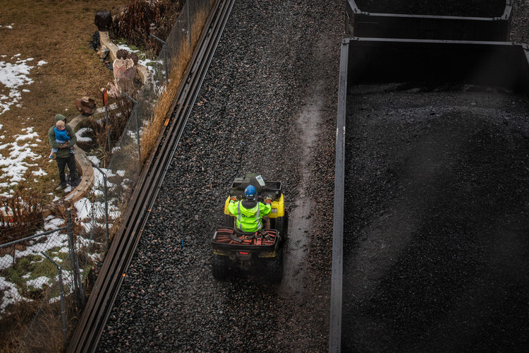 A Montana Rail Link worker rides down the line of train cars filled with coal while a man holds his son in the backyard of a home adjacent to the tracks.