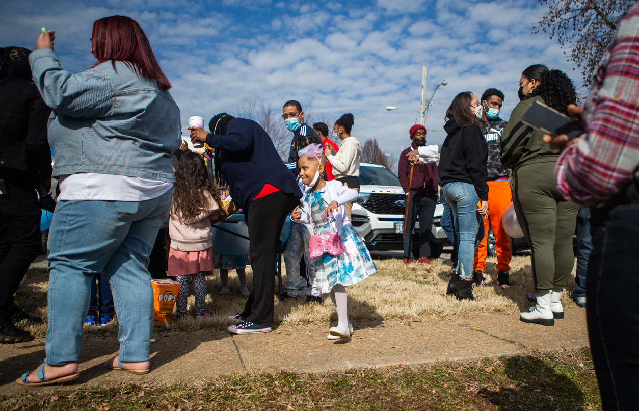 Paydenn Shelton, center, dashes around the gathered crowd to see her presents being dropped off after he birthday parade at January-Wabash Park in Ferguson on March 6, 2021