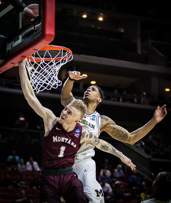 University of Montana junior guard Timmy Falls attempts a layup against University of Michigan senior guard Charles Matthews during the second half of the game. Falls was second in scoring for the Griz but only managed to put up 10 points in 28 minutes of play.