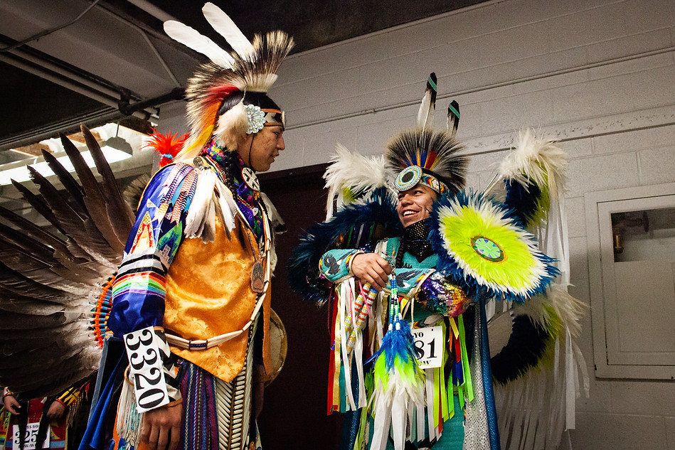Chaz Baker greets a friend in the tunnels below the arena while waiting to go on to dance in the Grand Entry.
