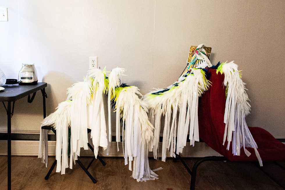 Two of Baker's bustles wait to be packed into the car to head to the powwow. Each bustle has 17 feathers on each side. Baker uses tape from JoAnn's craft store to keep the feathers in place. His color is teal, and he prefers bright colors to help the judges see him.