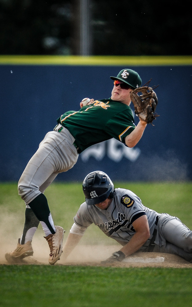 Missoula Mavericks' Stewart Long slides into second base, safe, while Lewis Clark Twins' Brayden Turcott narrowly avoids losing his balance on the base during the last few plays of the of the final game in the Memorial American Legion Baseball Tournament in Missoula, Montana on June 23, 2019.