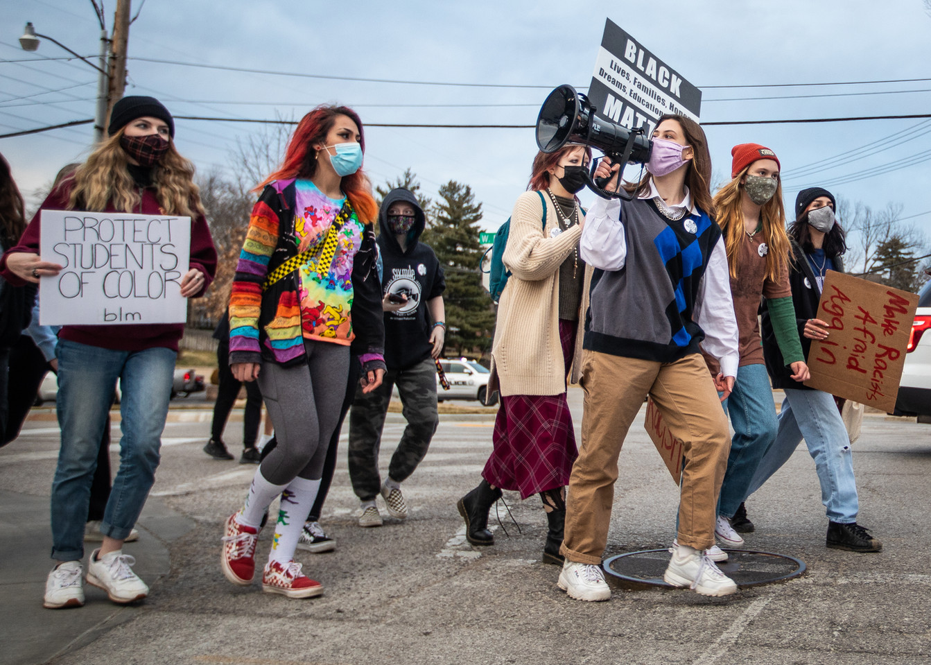Kirkwood High School sophomore and march co-organizer Kylie Madden, third from right, leads marchers in a chant as the group crosses Essex Avenue in Kirkwood, Missouri on Jan. 13, 2021. About 150 high school students and locals marched from Kirkwood High School to the Kirkwood Police Department to encourage prosecutors to take recent racist vandalism of the school seriously.