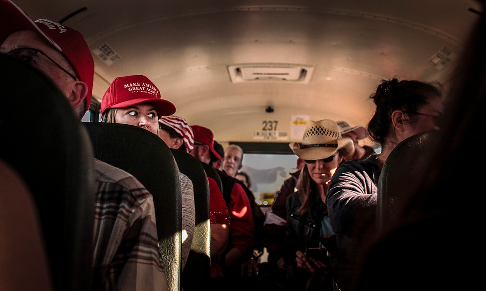 A woman watches the line of rally-attendees go past as she is bussed to the hangar after a three-hour wait in line.