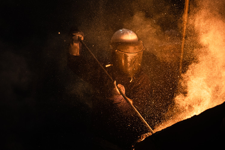 """A worker at Anaconda Foundry Fabrication Company tranfers molten menganese into a mold during a pour on March 3, 2020. The foundry in Ananconda, Montana, has been in constant operation since the days of the """"copper kings."""" One of many legacies of copper mining in the area, it is now an employee-owned operation and employs nearly a hundred Anacondans."""