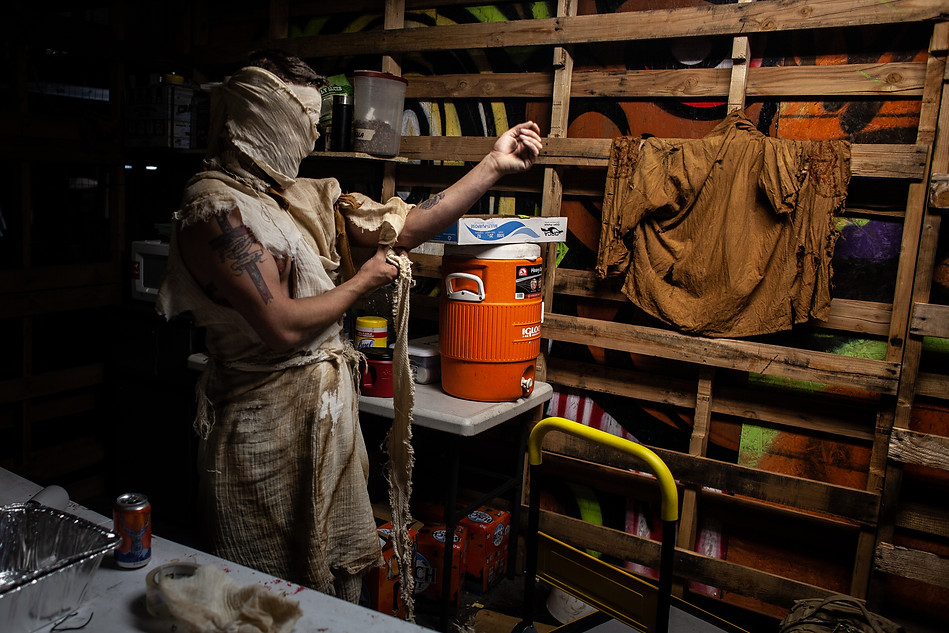 Haunt builder and scare-actor Bradley Lykins tries on his costume in the 'green room', a space where actors can refuel, apply makeup, and get water. The green room is accessible through the negative space easily for actors.