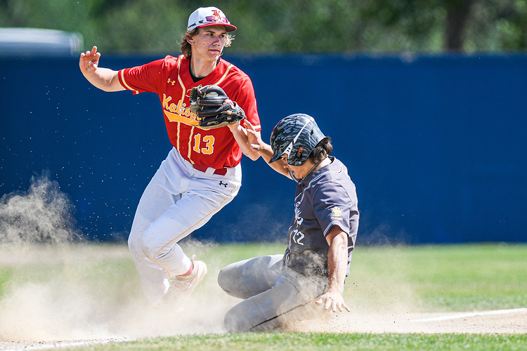 Kalispell Lakers' third baseman Ethan Diede catches the ball while Glacier's Devin Beale slides safely into third base during the fifth inning of the game. The game between the Lakers and the Twins at Lindborg-Cregg Field was the final one played before the Mavericks Memorial Tournament was shut down by the Missoula City-Country Health Department.