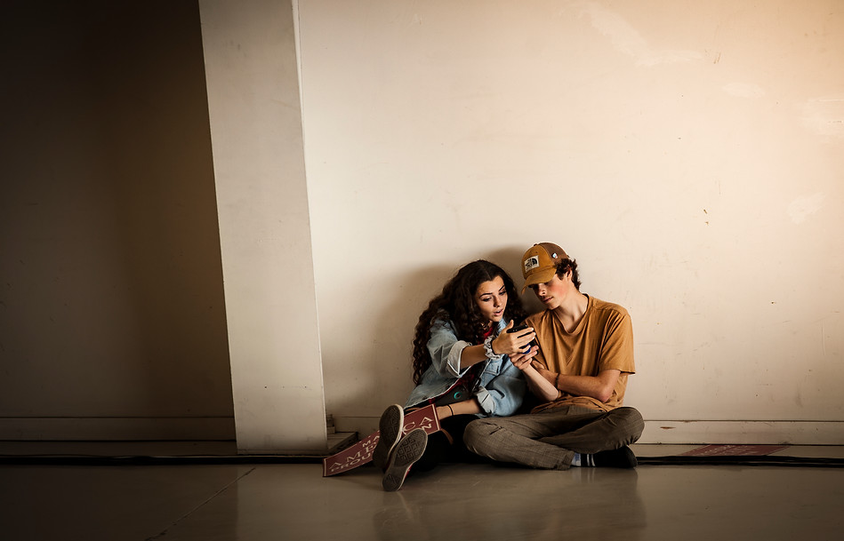 Two teens share a video on a phone while waiting for the rally to begin at about 5:15 p.m. The two sat against the west wall toward the back, and were soon joined by others as the hangar filled up and space to rest near the front became limited.