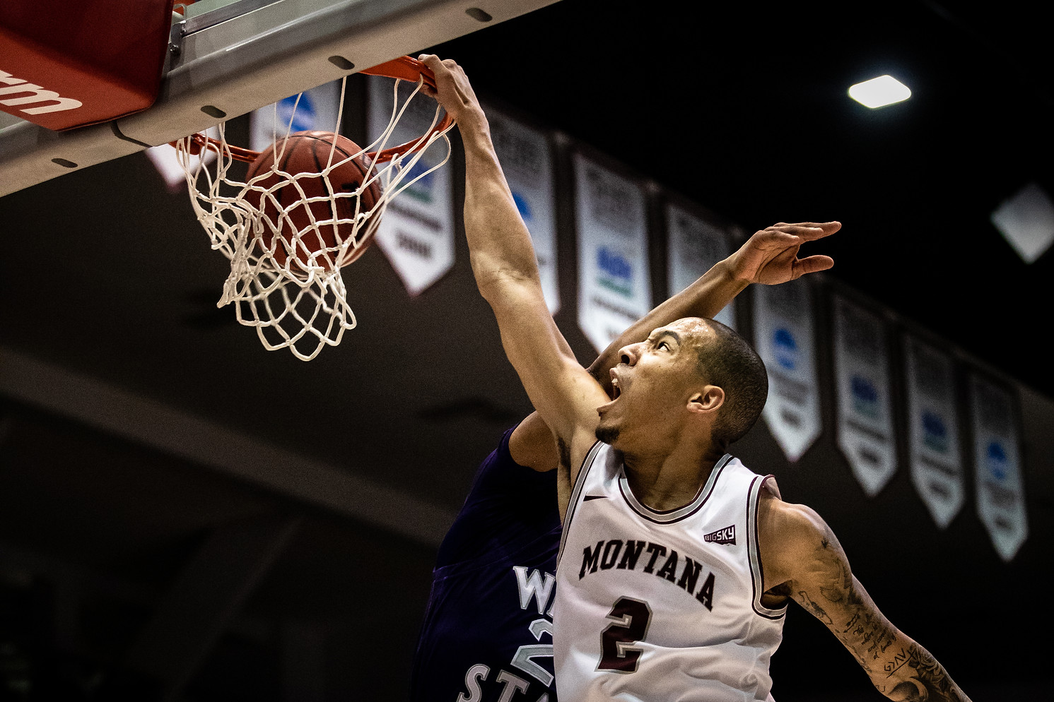 Montana senior guard Kendal Manuel dunks on a Weber State opponent after a fastbreak in the first half of the Griz 72-37 victory over Weber State on Feb. 18, 2020. The dunk marked Manuel's 1000th career point for the Griz.