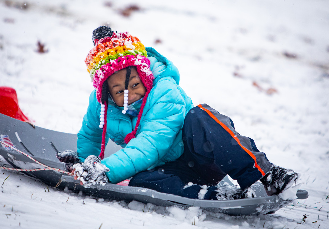 "Seven-year-old Kaylin Sanders picks up speed on her sled while enjoying the first big snowstorm of the year at Compton Hill Reservoir Park in St. Louis on Jan. 27, 2021. This was Sanders first time sledding. ""You have to be careful, or you could hurt your leg or your pinky like I did,"" she advised. Sanders says her favorite part of sledding is rolling in the snow when she falls off."