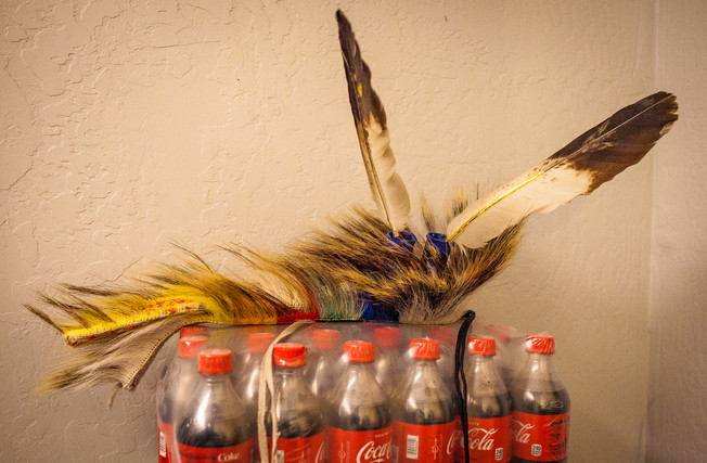 A rocker, a type of headdress regalia, sits atop soda bottles, safely off the ground to avoid being crushed in the crowded and busy dressing room, while Chaz and his siblings dress before their performance on April 14, 2019. Regalia can be passed down, gifted, or handmade, but is often emotionally valuable and made with important materials.