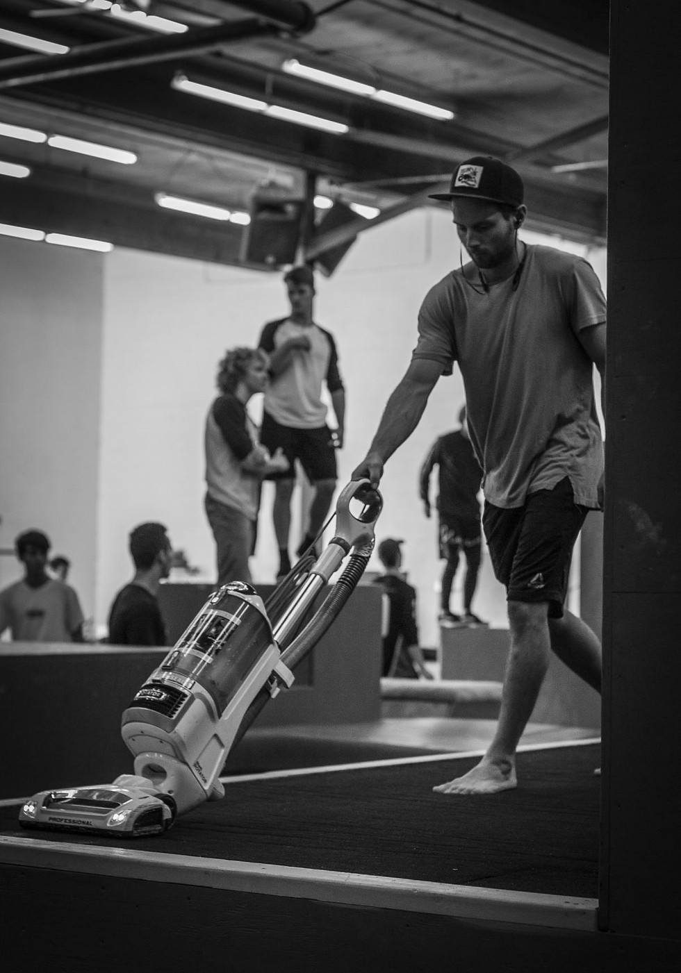 Marino vacuums the back corner of the gym on Oct. 19, 2018. Behind him, Balls Jam, the annual fall meet-up of athletes, starts up.  Unparalleled Movement was a massive financial venture for Marino, who lived and slept in the gym after first opening it to save money on rent. He says it was worth it, and that he enjoys the ability to be self-employed in a sport he cares about.