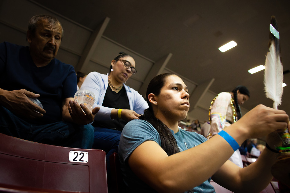 "Chaz Baker gazes across the arena as he fixes feathers on his headpieces while his mother, Rachel Topsky, braids his hair in preparation for Kyiyo Powwow grand entrance on April 19, 2019. Topsky, a dancer herself, watches her kids dance from the stands. ""It is everything to be a dancer,"" she said. ""When I'm dancing, there's nothing wrong in my life."""